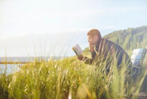 Man reading a book on a bench in the sunshine